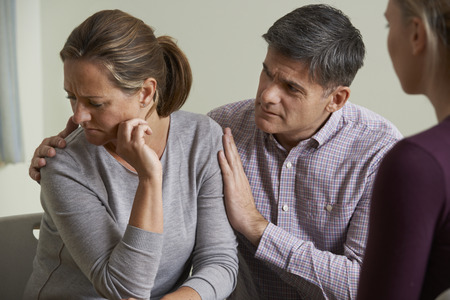 mature couple: Mature Couple Talking With Counsellor As Man Comforts Woman