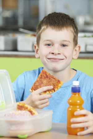 overweight students: Male Pupil Sitting At Table In School Cafeteria Eating Unhealthy Packed Lunch