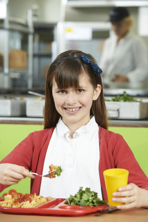 school cafeteria: Female Pupil Sitting At Table In School Cafeteria Eating Healthy Lunch