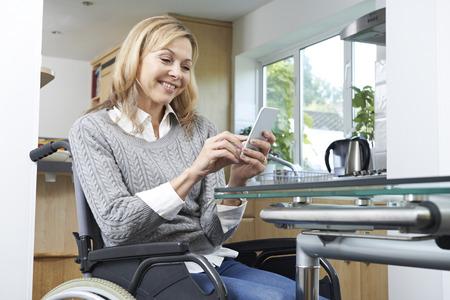 discapacidad: Mujer lisiada en mensajes de texto con silla de ruedas en el teléfono móvil en el hogar