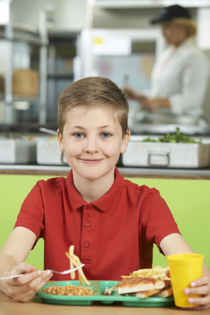 comedor escolar: Alumno Hombre sentado a la mesa en la cafetería de la escuela de la alimentación no saludable almuerzo Foto de archivo