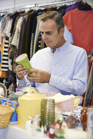 thrift: Male Shopper In Thrift Store Looking At Ornaments