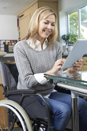 physical impairment: Disabled Woman In Wheelchair Using Digital Tablet At Home
