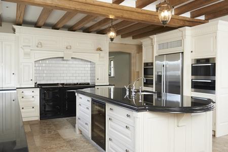 高級装備の梁のある天井が付いている家のキッチン