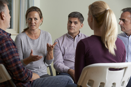 support group: Members Of Support Group Sitting In Chairs Having Meeting Stock Photo