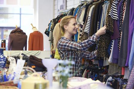 tienda de ropa: Comprador femenino En la tienda de descuento mirando la ropa Foto de archivo