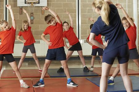 niños estudiando: Maestro toma la clase del ejercicio en gimnasia School Foto de archivo