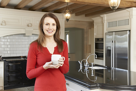 woman middle age: Mature Woman Standing In New Luxury Fitted Kitchen