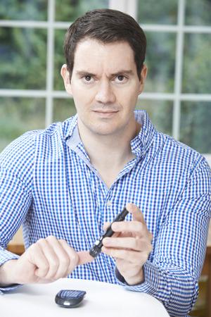 sick person: Man Checking Blood Sugar Level At Home