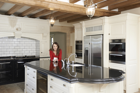 new age: Mature Woman Standing In New Luxury Fitted Kitchen