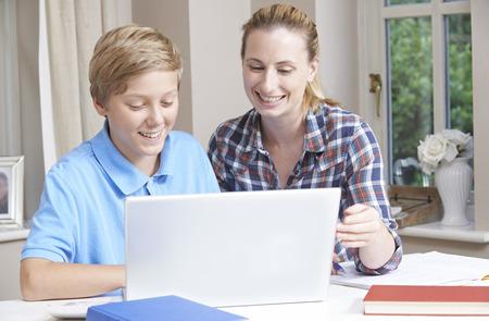deberes: Mujer Home Tutor Ayudar Boy con estudios usando el ordenador port�til