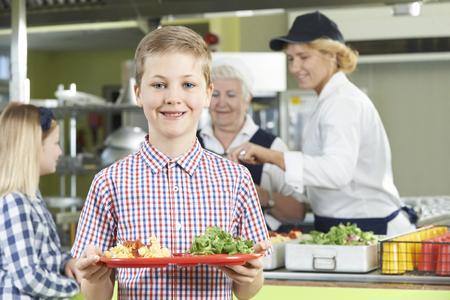 comedor escolar: Alumno de sexo masculino con almuerzo saludable en comedores escolares