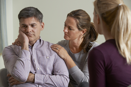 arguement: Mature Couple Talking With Counsellor As Woman Comforts Man Stock Photo