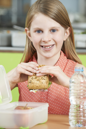 school cafeteria: Female Pupil Sitting At Table In School Cafeteria Eating Healthy Packed Lunch