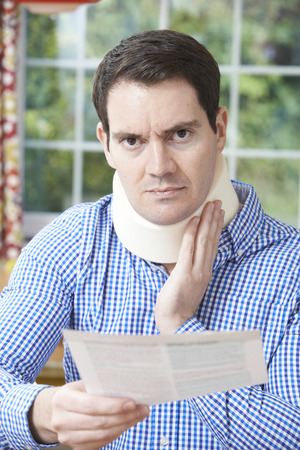 neck injury: Man Reading Letter After Receiving Neck Injury
