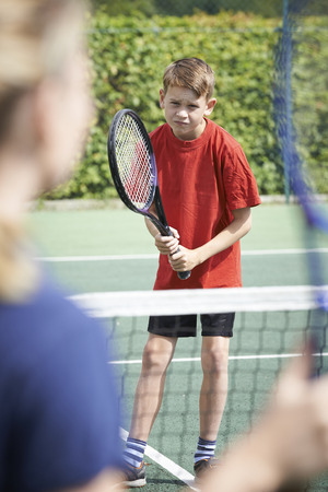 two children: Female Tennis Coach Giving Lesson To Boy