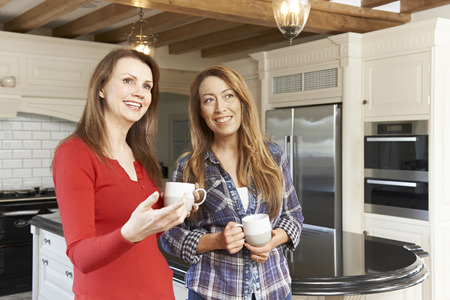 fitted: Mature Female Friends Standing In New Luxury Fitted Kitchen
