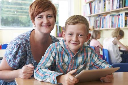 salle de classe: Élève de l'école avec l'enseignant l'aide du comprimé numérique dans la classe