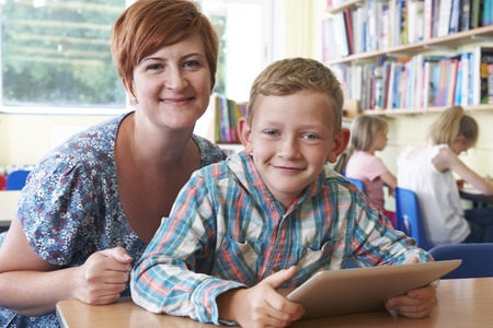 School Pupil With Teacher Using Digital Tablet In Classroom photo