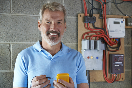 portrait: Portrait Of Electrician Standing Next To Fuseboard Stock Photo