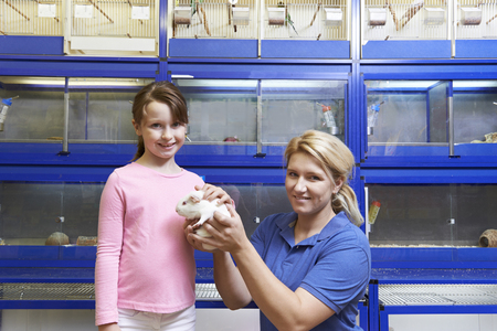 sales assistant: Sales Assistant Showing Girl Guinea Pig In Pet Store Stock Photo