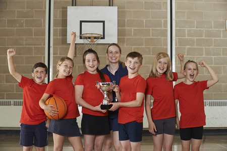 school sports: Victorious School Sports Team With Trophy In Gym Stock Photo
