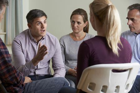 apoyo social: Miembros de ayuda del grupo sentados en sillas que tienen reunión