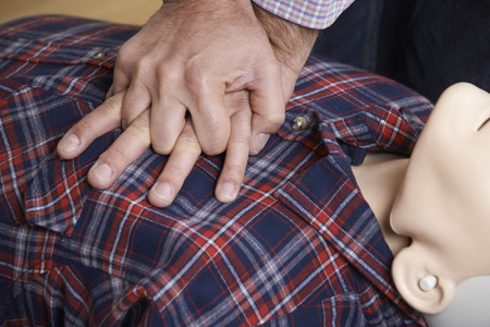 personne malade: Man Using CPR Technique Sur Dummy en premi�re classe de l'aide