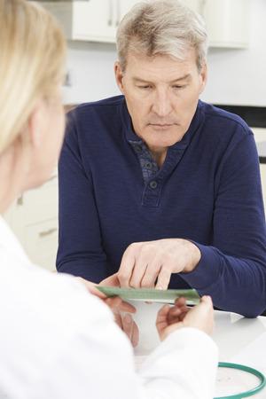 personas leyendo: Hombre maduro Folleto de Lectura En Consultorio médico Foto de archivo