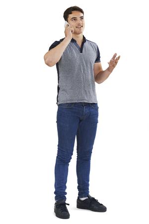 Studio Portrait Of Teenage Boy Talking On Mobile Phone