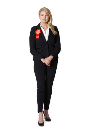 politician: Full Length Portrait Of Female Politician Wearing Red Rosette Stock Photo