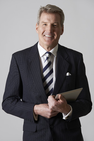 Studio Portrait Of Mature Businessman Holding Digital Tablet