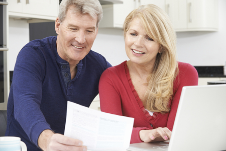 fifties: Smiling Mature Couple Reviewing Domestic Finances