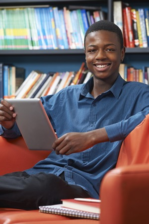 smiling teenagers: Male Teenage Student Using Digital Tablet In Library Stock Photo