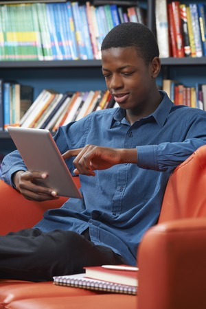 secondary school: Male Teenage Student Using Digital Tablet In Library Stock Photo