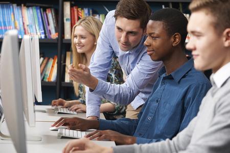 profesor alumno: Tutor que trabaja con el Grupo de estudiantes adolescentes usando los ordenadores Foto de archivo