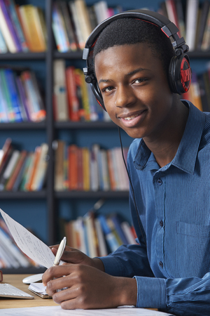 male teenager: Teenage Student Wearing Headphones Whilst Working In Library Stock Photo