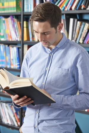 textbook: University Student Reading Textbook In Library Stock Photo
