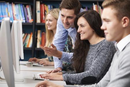 monitor de computadora: Tutor Ayudar a Estudiantes adolescentes trabajan en los ordenadores Foto de archivo
