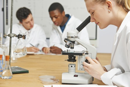 Teenage Students In Science Class Using Microscope