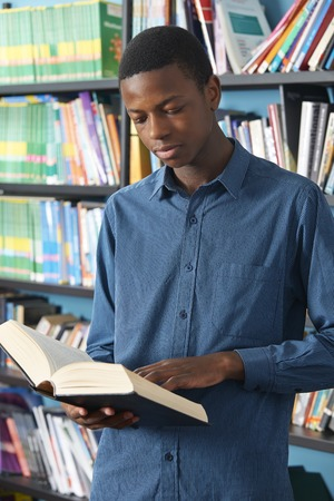 secondary education: Male Teenage Student Reading Book In Library Stock Photo