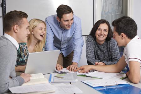 secondary school teacher: Teacher Working In Classroom With Students