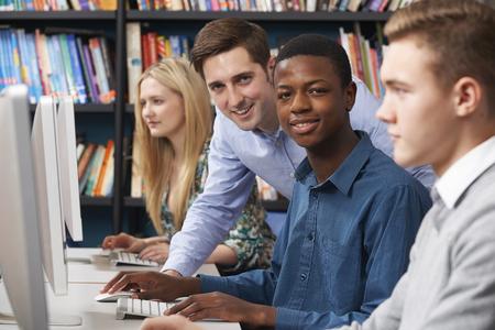 hombres jovenes: Tutor con grupo de estudiantes adolescentes usando los ordenadores