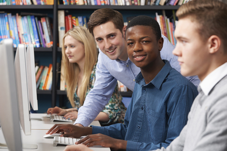 young man: Tutor With Group Of Teenage Students Using Computers