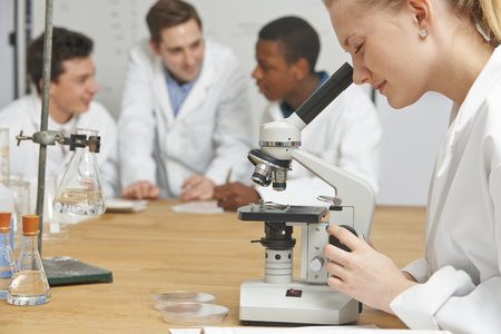 secondary schools: Female Pupil Using Microscope In Science Lesson