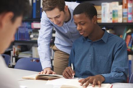 教師が教室で男子生徒を支援