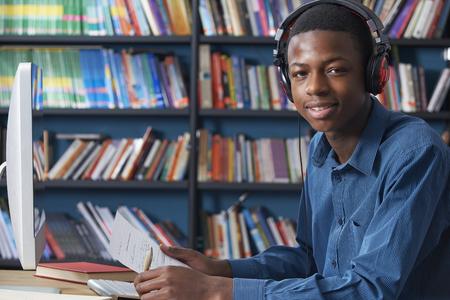 Male Teenage Student Working At Computer Wearing Headphones Foto de archivo