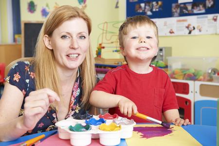 educator: Teacher Helping Preschool Child In Art Class