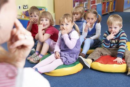 Group Of Children Copying Teacher In MontessoriPre-School Class
