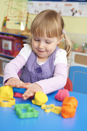 pre school: Female Pre School Pupil Playing With Modelling Clay Stock Photo